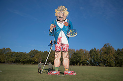 © Licensed to London News Pictures. 31/10/2018. Edenbridge, UK. Artist Andrea Deans stands on a ladder next to an effigy of former foreign secretary Boris Johnson as it is unveiled in Edenbridge, Kent ahead of its burning at the town's bonfire this Saturday. The 10 meter high figure stands over two EU referendum buses and Boris is also carrying an EU cake. Photo credit: Peter Macdiarmid/LNP