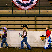 """Breanna Robbins, left, Jaycie Rauch, center, and Drake Israel, right, walked around the show ring at the American Royal's Hale Arena  during the stick horse """"competition"""" at the Quarter Horse Show. All the entrants received blue ribbons for their equestrian skills."""
