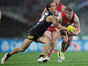 Daniel Hannebery of the Swans is tackled during the 2013 AFL Round 14 match between the Sydney Swans and the Carlton Blues at the SCG, Sydney on June 28, 2013. (Photo: Craig Golding/AFL Media)