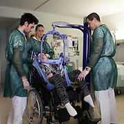 Santa Lucia Foundation, Rome, February 20, 2016. 21-year-old Chiara Insidioso Monda,  in a state of semi-consciousness because of violent beatings by her former 'partner', 16 years older than her, today needs a h24 assistance. Here she is helped by the hospital staff to move from the wheelchair to the bed, an operation that is repeated several times a day.<br /><br />Fondazione Santa Lucia, Roma, 20 Febbraio 2016. Il personale della Fondazione Santa Lucia aiuta Chiara nel passare dalla sedia a rotelle al letto attraverso il sollevatore.