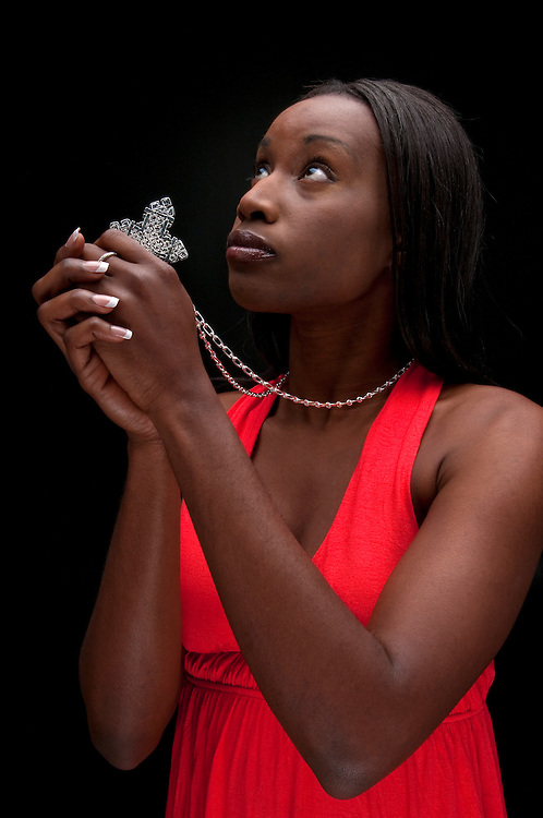 Young african american woman praying with faith and hope.
