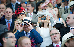 © licensed to London News Pictures. 14/06/2011. Ascot, UK.  Crowds watch the first race on Day one at Royal Ascot races today (14/03/2011). The 5 day showcase event,  one of the highlights of the racing calendar is in it's 300th year. Horse racing has been held at the famous Berkshire course since 1711 and tradition is a hallmark of the meeting. Top hats and tails remain compulsory in parts of the course. Photo credit should read: Ben Cawthra/LNP
