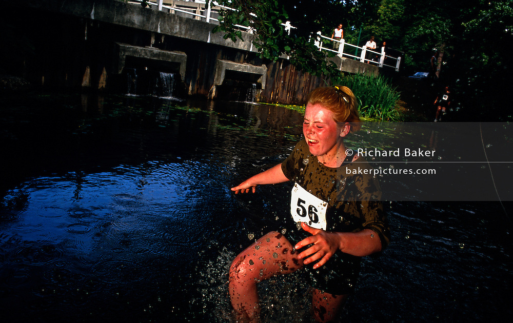 With a grimace on her pained face, a female Officer Cadet at the Royal Military Academy Sandhurst splashes through a water obstacle during  an endurance race. Recruits are running a 5 mile steeplechase around the Academy grounds to assess individual stamina and accumulate team points. Sandhurst is an institution which has bred staff officers since 1800. Today it trains future officers for the demands of leadership and military understanding of military understanding. Students are tested for their command instincts, intellect, strength of character and physical endurance often under great psychological pressure - the demands asked of them in modern warfare. Failure in this test might not necessarily mean dismissal though perseverance or refusal to give up won't harm their prospects.