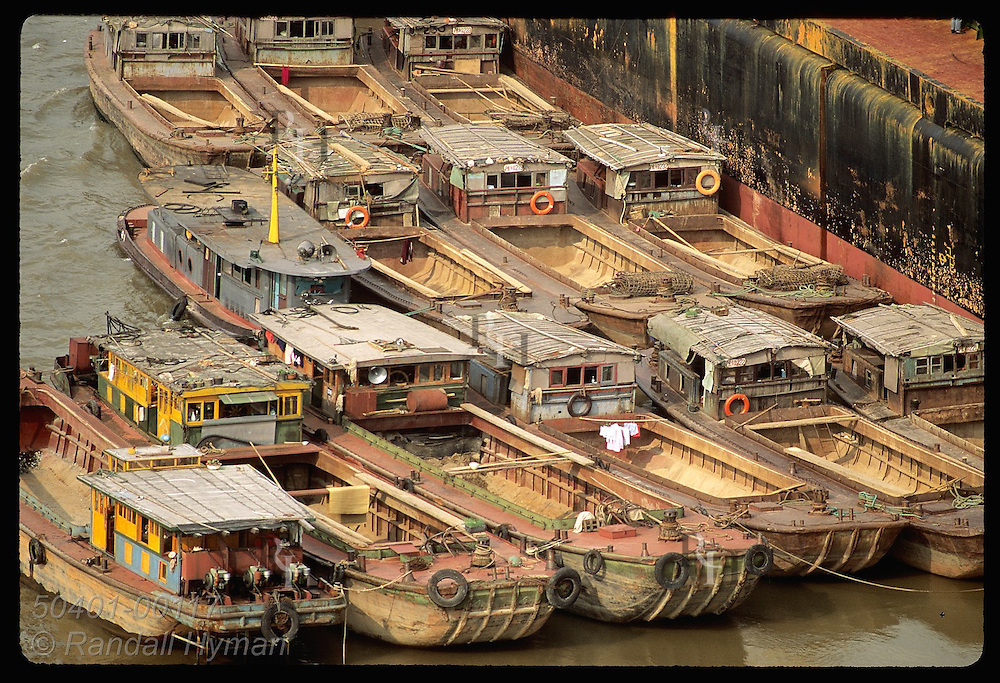 Barges dock in a huddle along hull of ocean freighter on the Huangpu River in Shanghai. China