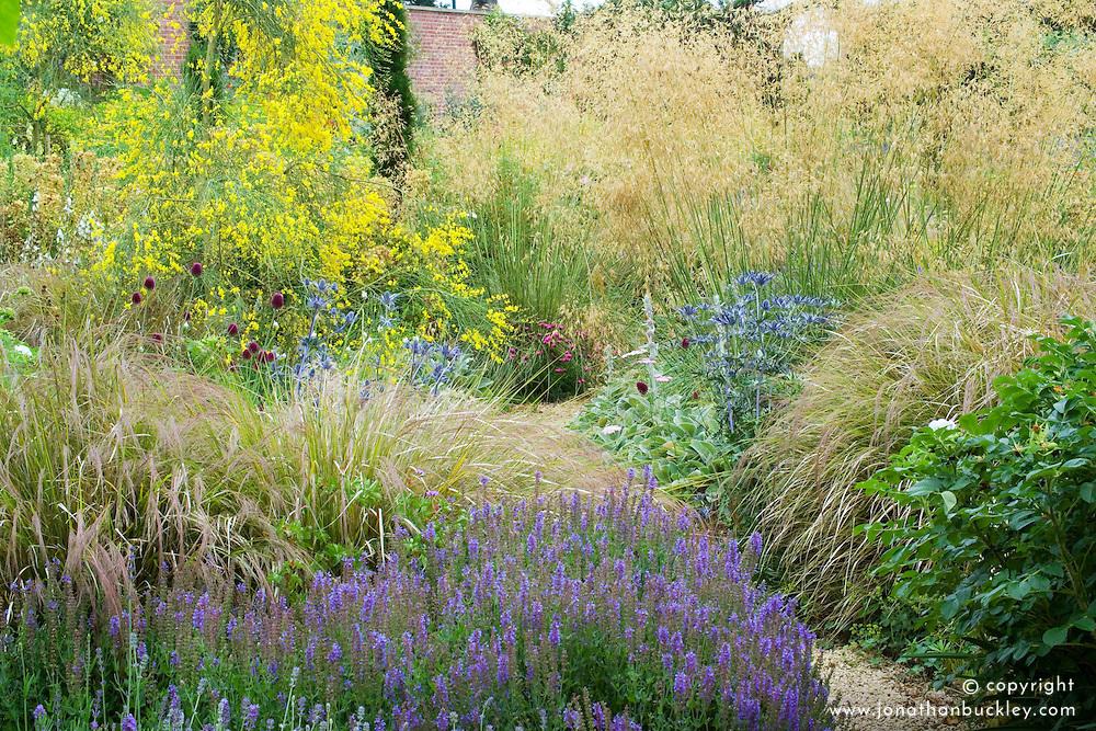 Borders of grasses and perennials at Broughton Grange including Stipa gigantea