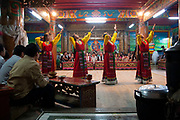 Traditional music and dancing put on for tourists in Zhongdian, Yunnan, China. Minority people wear traditional dress amongst a very vocal crowd who drink a hot sour milk soup and shots of Bai Jiu.