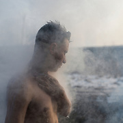 An afghani migrant washes himself with water heated on an open fire outside a warehouse near Belgrade's main railway station. Some days the temperatures here drop to -15 degrees Celsius.