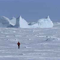 BAFFIN ISLAND, CANADA. Alex Lowe (MR) & iceberg on frozen Baffin Bay, near Clyde River in Nunavut.