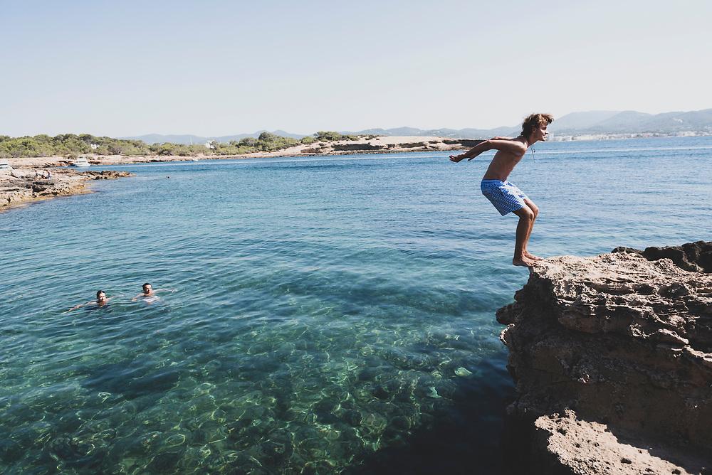 Cala Gració, Ibiza, Spain - July 30, 2018: A young man begins to do a backflip from a rocky outcrop at Cala Gració, in Ibiza, Spain.