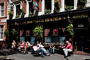 People sitting outside the Sherlock Holmes pub on Northumberland Avenue, London. The name and position of this pub means it is a big draw for tourists.