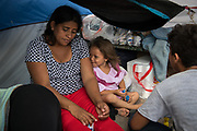 A migrant mother from El Salvador and her three year-old daughter, asylum seekers sent back to Mexico from the U.S. under Migrant Protection Protocols (MPP), pass the time in their tent at a makeshift encampment near the U.S. port of entry at the Gateway International Bridge in Matamoros, Tamaulipas, Mexico, August 24, 2019.