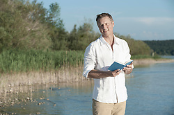 Mature man reading book and smiling at lakeside, Bavaria, Germany