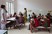 A scene of Nepalese mothers feeding their children nutritious food during a meal time in the dining room at the Friends of Needy Children Nutritional Rehabilitation Centre, Kathmandu, Nepal.  <br /> The children are all malnourished and are inpatients in the centre and receiving intensive treatment for malnutrition. The centre has recently been built to provide healthcare to malnourished children and education to mothers about nutrition and childcare. A female nurse observes the room to monitor all the children's progress.