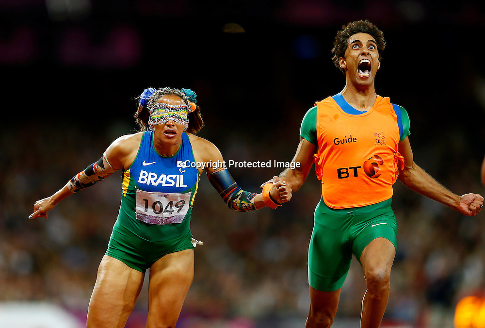 Terezinha Guilhermina (L) of Brazil and her guide Guilherme Soares de Santana (R) reacts after crossing the finish line in Women's 100m -T11 final at the Olympic Stadium during the London 2012 Paralympic Games, London, Britain, 05 September 2012. Guilhermina won the gold medal.  EPA/KERIM OKTEN