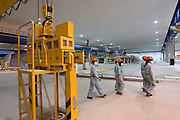 Chinese workers walk past a Standard Duty 8 ton Kone Crane part Oji Paper Factory's assembly line, in Nantong, Jiangsu province, China, on May 25, 2010. Photo by Lucas Schifres/Pictobank