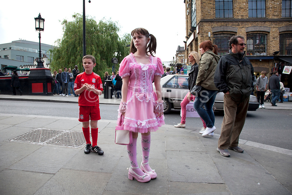 LONDON, ENGLAND, UK, JUNE 11TH 2011. Georgia (11, wearing a pink Lolita dress) and brother Kiefer (8, wearing a red Liverpool Football Club kit) spending a day out together in Camden Town, North London. Louise (their mother) is on various benefits to help support her family income, and housing, although recent government changed to benefits may affect her family drastically, possibly meaning they may have to move out of London. Louise Ryan was born on the Wirral peninsula in 1970.  She moved to London with her family in 1980.  Having lived in both Manchester and Ireland, she now lives permanently in North London with her husband and two children. Through the years Louise has battled to recover from a serious motorcycle accident in 1992 and has recently been diagnosed with Bipolar Affective Disorder. (Photo by Mike Kemp/For The Washington Post)