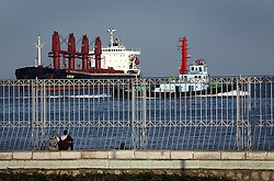 A couple watches ships pass through the Suez Canal in Port Said, Egypt on April 7, 2008. The canal is one of the most important shipping routes in the world, as it allows two-way water transportation - most importantly between Europe and Asia without the circumnavigation of Africa.