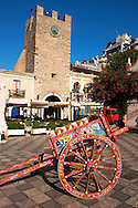 Traditional Sicilian cart infront of the gate tower on  on the Plaza ix Aprile with trees in blossom - Taormina, Sicily .<br /> <br /> Visit our SICILY PHOTO COLLECTIONS for more   photos  to download or buy as prints https://funkystock.photoshelter.com/gallery-collection/2b-Pictures-Images-of-Sicily-Photos-of-Sicilian-Historic-Landmark-Sites/C0000qAkj8TXCzro