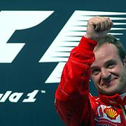 Ferrari's Rubens Barrichello salutes the crowd at the top of the podium