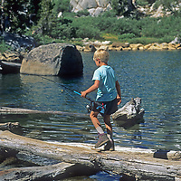 A young fisherman crosses a log at the outlet of Fifth Lake in Big Pine Canyon in California's eastern Sierra Nevada.