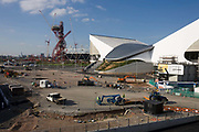 Landscape of 2012 Olympic construction site showing the Aquatic centre, The Orbit art tower and the main stadium at Stratford. Construction workers offload a low crane from a ramp in a section of road outside the curved architecture of the Aquatic centre, seen with its white roof.  The London Olympic Stadium will be the centrepiece of the 2012 Summer Olympics and Paralympics. The stadium has capacity for the Games of approximately 80,000 making it temporarily the third largest stadium in Britain. The ArcelorMittal Orbit Tower is the newest addition to the Olympic Park and provides an attraction to rival those visited the world over. The Orbit tower gives views over the Park and the rest of London, it also caters for events and conferences offering delegates and organisers alike a unique setting and location for their event.