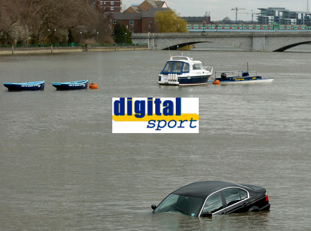 Photo: Daniel Hambury.<br />Varsity Boat Race Preview Day. 29/03/2006.<br />A black BMW car caught out by the high tide floats down the Thames.
