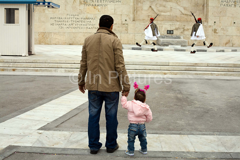A father and his daughter watch two Greek soldiers perform the Changing of the Guard in front of the Tomb of the Unknown Soldier. The marble relief in the background is a copy of an ancient warrior grave stele, depicting a hoplite lying dead on a small slab.