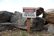 large Danger keep off the rocks sign warning people to stay of the rocks