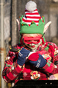"""05 DECEMBER 2020 - INDIANOLA, IOWA: A child dressed as a Christmas elf works on toys in """"Santa's Workshop"""" during a drive through visit with Santa Claus. About 500 children visited Santa Claus and Mrs. Claus in Indianola Saturday. The town has hosted Santa on the town square for the last seven years but the COVID-19 (SARS-Cov-2) pandemic forced organizers to move the event to the parking lot of a local hardware store and do it """"drive through"""" style. Iowa has one of the highest Coronavirus test rates in the United States.        PHOTO BY JACK KURTZ"""