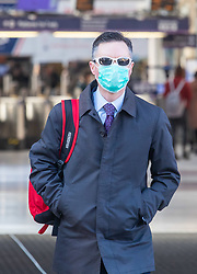 © Licensed to London News Pictures. 16/03/2020. London, UK. A London commuter on his way to work in a mask at a quiet Victoria Station this morning as Government ministers warn that over 70s will face self-isolation for weeks as the Coronavirus disease pandemic continues . Photo credit: Alex Lentati/LNP