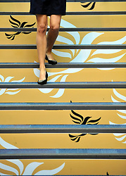 © Licensed to London News Pictures. 20/09/2011. BIRMINGHAM, UK.  A woman walks down a set of stairs featuring Liberal Democrat brandingat the Liberal Democrat Conference at the Birmingham ICC today (20 Sept 2011): Stephen Simpson/LNP . Photo credit : Stephen Simpson/LNP