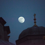 A silhouette of some of the rooftop of the New Mosque in front of the moon in the night sky. Situated in the busy Eminonu quarter of Istanbul, at the southern end of the Galata Bridge, the New Mosque (or Yeni Cami) dates to around 1665. It's large prayer hall is decorated in the distinctive Ottoman imperial style.