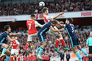 Shkodran Mustafi of Arsenal jumps up to head the ball from a cross over George Friend of Middlesbrough and Gaston Ramirez of Middlesbrough. Premier league match, Arsenal v Middlesbrough at the Emirates Stadium in London on Saturday 22nd October 2016.<br /> pic by John Patrick Fletcher, Andrew Orchard sports photography.