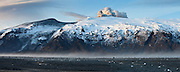 A panorama view of Eyjafjallajökull erupting volcano in south Iceland 2010. <br /> View from Fljótshlíð at sunrise. Stranded icecubes in foreground after a flod in Markarfljót