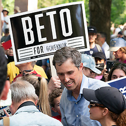 """Former Congressman and presidential candidate BETO O'ROURKE works his way through the crowd as someone holds a """"Beto for Governor"""" sign after a thousand Texas Democrats rally at the State Capitol supporting voting rights bills stalled in Congress and decrying Republican efforts to thwart voter registration and access to the polls."""