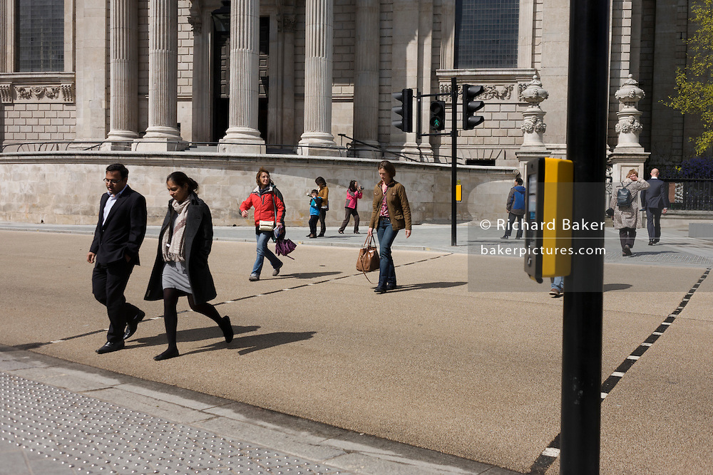Pedestrians walk across a road crossing point below the pillars and columns of St Paul's Cathedral in Central London.
