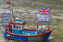 London Bridge, London, June 15th 2016. A flotilla of fishing boats led by UKIP's Nigel Farage heads through Tower Bridge in protest against the EU's Common Fisheries Policy and in support of Britain leaving the EU. PICTURED: A small fishing boat's banner claims the Common Fisheries Policy has been aa economic, social and environmental disaster for British fishermen