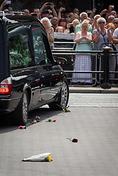© Licensed to London News Pictures . 12/07/2013 . Bury , UK . Onlookers throw flowers in the path of the hearse carrying Lee Rigby's coffin , after the service . The funeral for Fusilier Lee Rigby at Bury Parish Church in Bury town centre today (Friday 12th July 2013) , watched by 100s of people . Fusilier Rigby's coffin was held in Bury Parish Church overnight , watched over by an honour guard of soldiers from the 2nd Battalion Royal Regiment of Fusiliers ( 2RRF ) . Rigby was brutally murdered in Woolwich , London on 22nd May 2013 . Photo credit : Joel Goodman/LNP