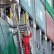 Nederland Zuid-Holland Rotterdam  27-08-2009 20090827 Foto: David Rozing .Serie over logistieke sector.Reusachtige zeeschepen aan de kade worden gelost en geladen. Bedrijvigheid havenarbeider, man tilt pakket via een loopbrug naar het schip. ECT Delta terminal in de haven van Rotterdam. .ECT,European Container Terminals, at the Port of Rotterdam. Europe's biggest and most advanced container terminal operator, handling close to three- quarters of all containers passing through the Port of Rotterdam. ECT is a member of the Hutchison Port Holdings group (HPH), the world biggest container stevedore with terminals on every Continent , zeeschip, zeevaart, zwaar, zwaar beroep, zwaar werk, zware, zware beroepen.Holland, The Netherlands, dutch, Pays Bas, Europe .Foto: David Rozing