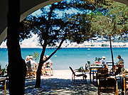 People sitting at tables on terrace by the Mediterranean Sea, San Antonio, island of Ibiza, Balearic Islands, Spain, 1950s