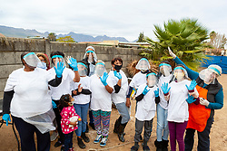 """Volunteer ladies and youth wave at a """"Safe Zone"""" in Vanwyk'svlei, Wellington, Western Cape, South Africa.(Picture: JULIAN GOLDSWAIN)"""