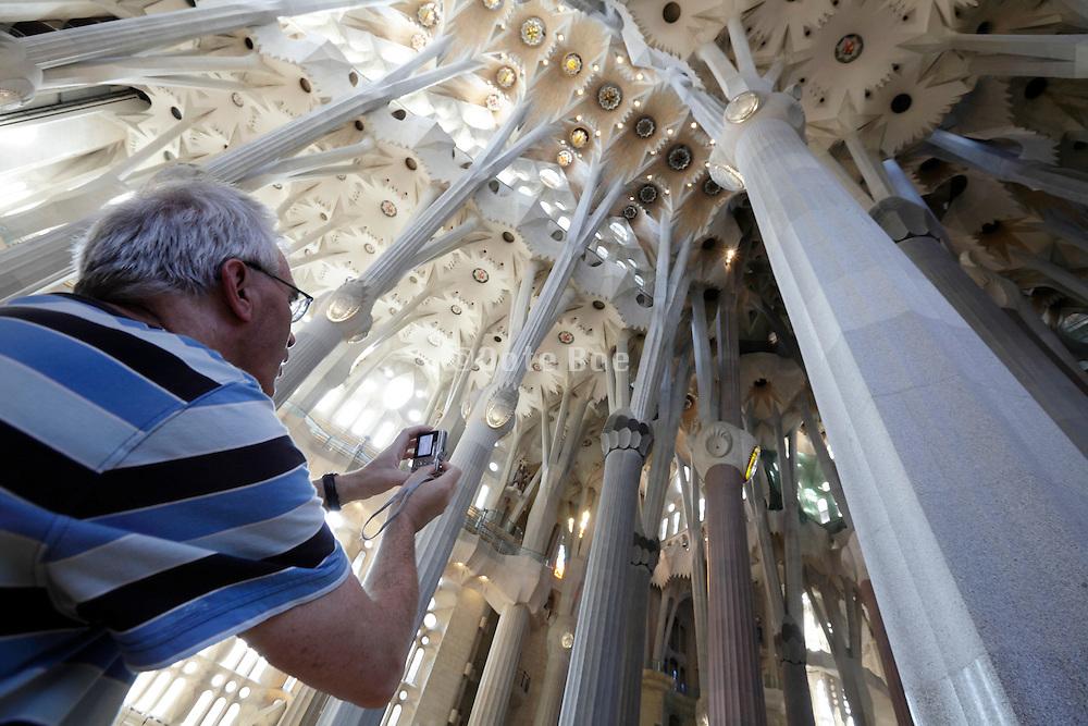 tourist photographing ceiling Sagrada Familia Barcelona Spain