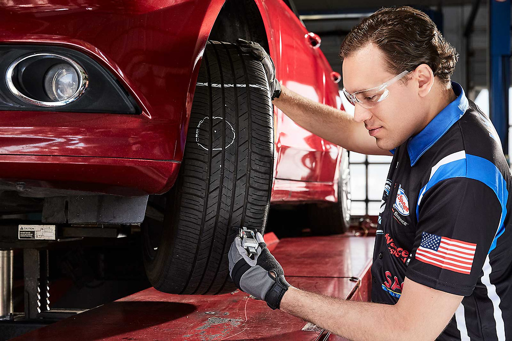 Raymond Rudolph photographs a mechanic checking tires during an advertising photoshoot for Speedee-Midas.