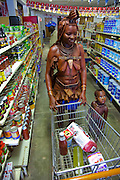 """A traditionally dressed Himba woman shops for staples and soda pop with her child in a supermarket in Opuwo, a town well known for cultural tourism in northwestern Namibia, after receiving money from a tourist in exchange for a photograph.  Like most traditional Himba women, she covers herself from head to toe with an ochre powder and cow butter blend. Some Himba are turning to tourism to kick-start their entry into the cash economy, setting up demonstration villages advertising """"The Real Himba."""""""