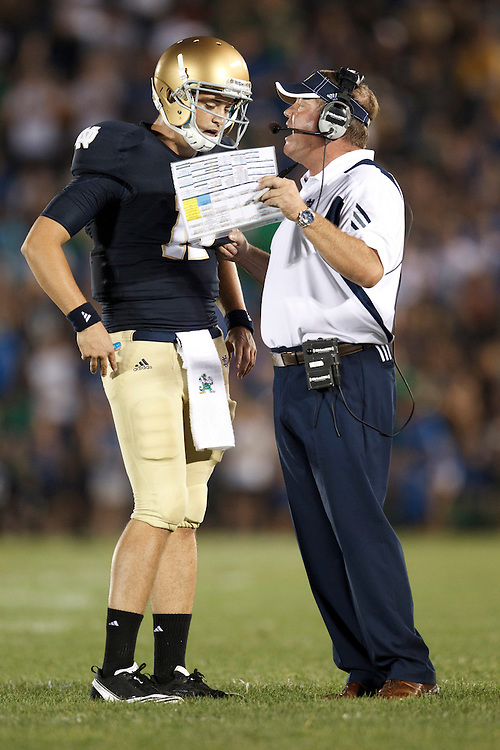 Notre Dame head coach Brian Kelly gives quarterback Tommy Rees (#11) play instructions during NCAA football game between Notre Dame and South Florida.  The South Florida Bulls defeated the Notre Dame Fighting Irish 23-20 in game at Notre Dame Stadium in South Bend, Indiana.