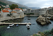 Elevated view from Fortress Lovrinjenac (Fort of Saint Lawrence) of Dubrovnik's oldest harbour, Kalarinja, with Dubrovnik old town and Fortress Bokar in background