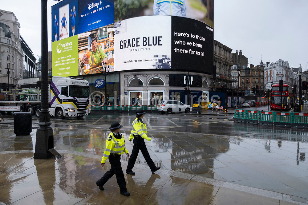 Police patrol a very quiet Piccadilly Circus during a rain shower under coronavirus lockdown on 1st July 2020 in London, England, United Kingdom. As the July deadline approaces and government will relax its lockdown rules further, the central London remains very quiet, while some non-essential shops are allowed to open with individual shops setting up social distancing systems.