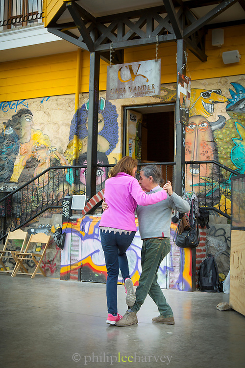 Couple dancing tango on street in front of building, Valparaiso, Chile