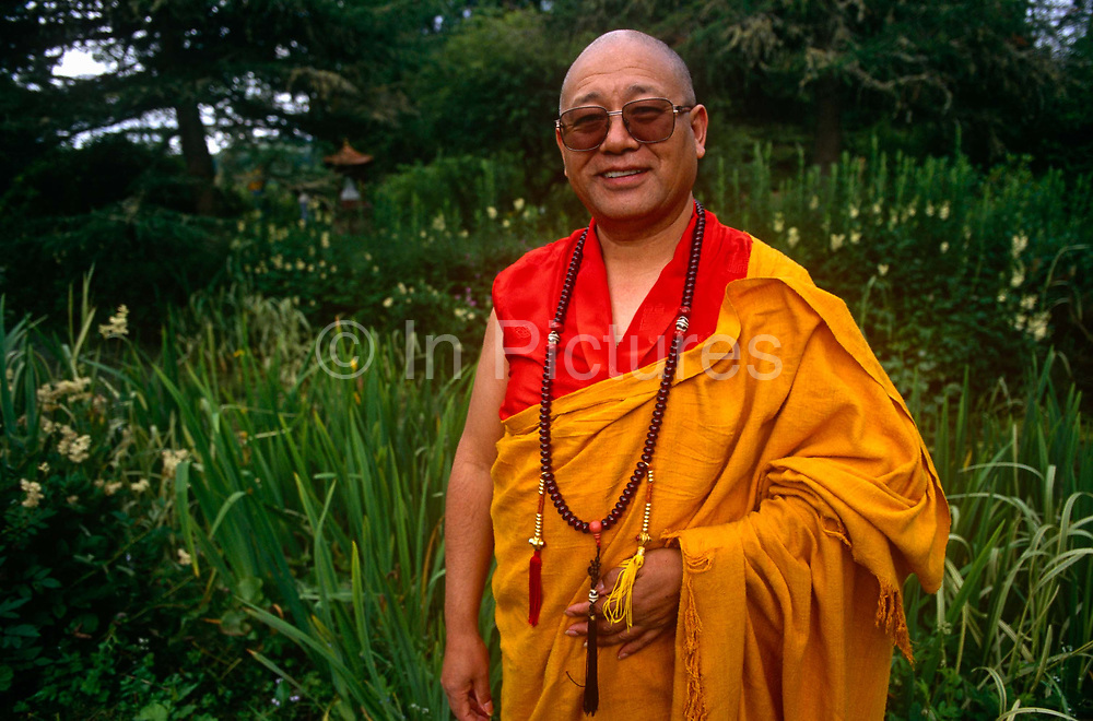 A portrait of the Tibetan-Buddhist Lama Yeshe Losal Rinpoche standing in gardens of Samye Ling Buddhist Centre, Scotland. Looking relaxed and at peace with himself, the spiritual leader wears the robes and necklace of a Buddhist monk with a background of green grasses and reeds. Lama Yeshe Losal Rinpoche is a lama in the Kagyu school of Tibetan Buddhism and abbot of the Samye Ling Monastery, Scotland, the first and largest of its kind in the West.