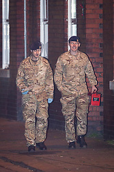 © Licensed to London News Pictures . 28/11/2013 . Manchester , UK . Men in army fatigues walk towards the house . Scene at 17 Mellor Street in Eccles , Greater Manchester this evening (Thursday 28th November 2013) where police have cordoned off adjoining streets and evacuated houses following the discovery of a suspicious device .  Photo credit : Joel Goodman/LNP